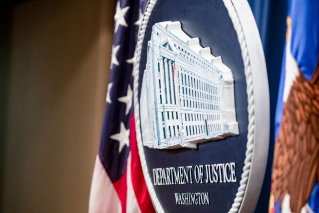 WASHINGTON, DC - DECEMBER 05: The U.S. Department of Justice seal on the stage where U.S. and U.K. Law enforcement officials will announce warrants for the arrests of Maksim Viktorovich Yakubets and Igor Olegovich Turashev, two Russian hackers associated with a group called Evil Corp., at the U.S. Department of Justice on December 5, 2019 in Washington, DC. Today the U.S. Department of Justice, Federal Bureau of Investigations (FBI), and the U.S. Treasury Departments Office of Foreign Assets Control (OFAC) took action against Evil Corp, the Russia-based cybercriminal organization responsible for the development and distribution of the Dridex malware. (Photo by Samuel Corum/Getty Images)
