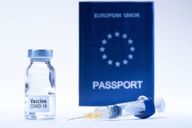 "TOPSHOT - A picture taken on March 3, 2021 in Paris shows a vaccine vial reading ""Covid-19 vaccine"" and a syringe next to an European passport. (Photo by JOEL SAGET / AFP) (Photo by JOEL SAGET/AFP via Getty Images)"