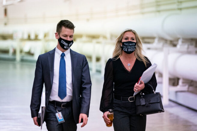 """WASHINGTON, DC - FEBRUARY 25: Rep. Marjorie Taylor Greene (R-GA) wears a protective mask bearing the words """"This mask is as useless as Joe Biden,"""" as she walks with an aide to a vote in the Cannon Tunnell on Capitol Hill, on February 25, 2021 in Washington, DC. (Photo by Al Drago/Getty Images)"""