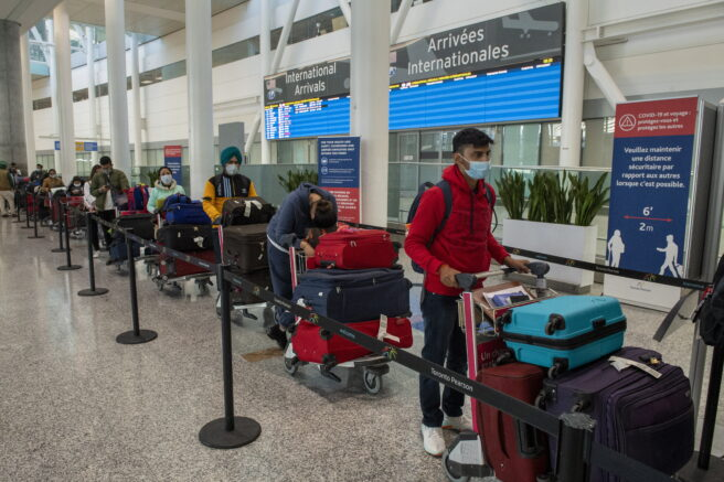 Passengers from New Delhi wait in long lines for transportation to their quarantine hotels at Pearson Airport in Toronto on Friday April 23, 2021. Flights from India and Pakistan to Canada have been suspended for 30 days. (Frank Gunn/The Canadian Press via AP)