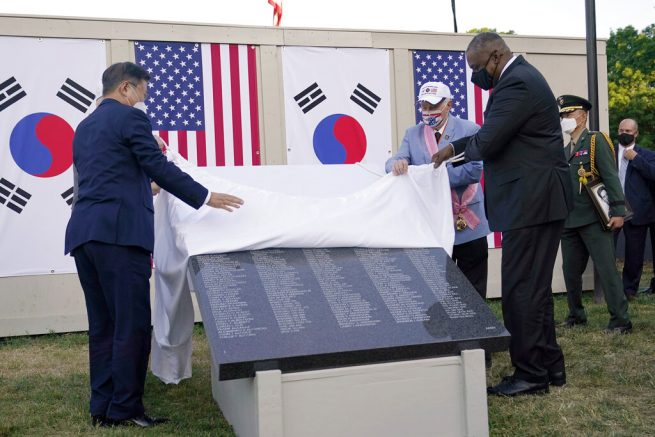 South Korean President Moon Jae-in, left, and Secretary of Defense Lloyd Austin, right, look at a replica of a section of the Wall of Remembrance at the Korean War Veterans Memorial in Washington, Friday, May 21, 2021, during a groundbreaking ceremony. The Korean War Veterans Memorial Wall of Remembrance is a long-planned addition to the existing Korean War Veterans Memorial and will display the names of the U.S. military and Korean Augmentation to the United States Army personnel who gave their lives defending South Korea's people from aggression and ensuring their freedom. (AP Photo/Susan Walsh)