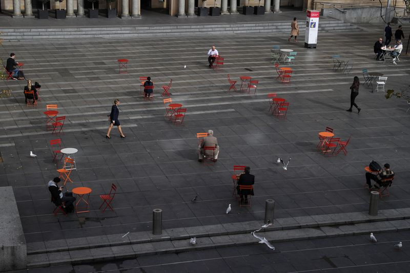 People sit at socially distanced tables as an outbreak of COVID-19 affects Sydney