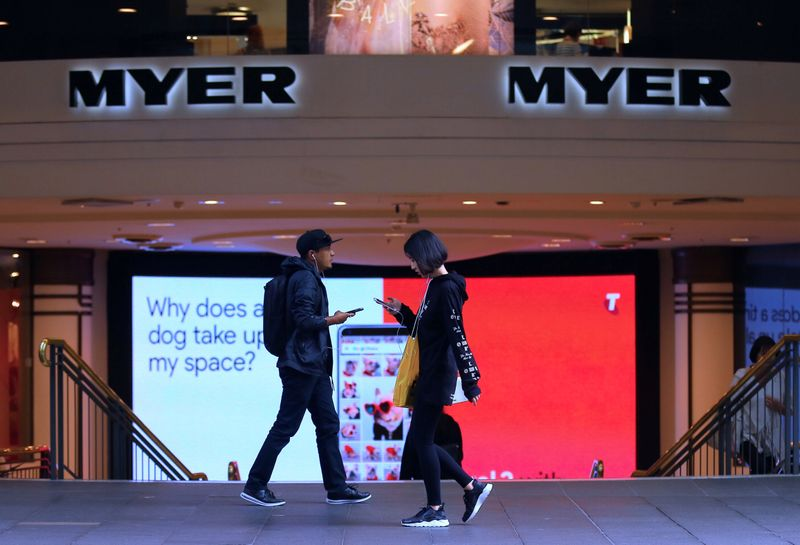 Shoppers use their phones as they walk past the entrance to a Myer department store in Sydney