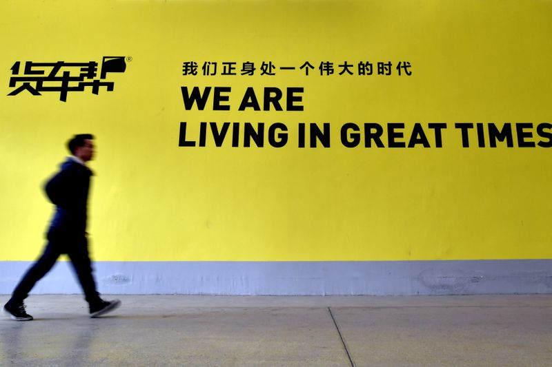 FILE PHOTO: A man walks past a sign of Huochebang or Truck Alliance, an app for truck services, in Guiyang
