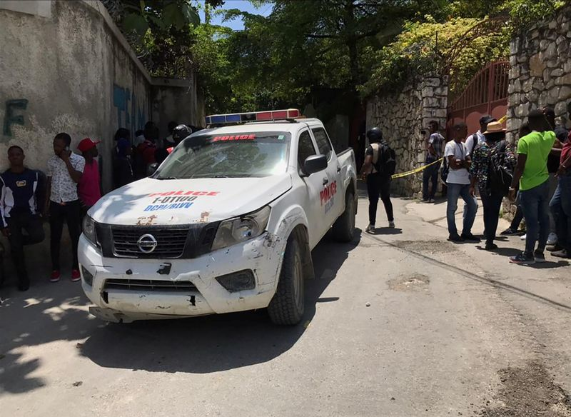 People stand next to a police car near the residence of Haiti's President Jovenel Moise after he was shot dead by unidentified attackers, in Port-au-Prince