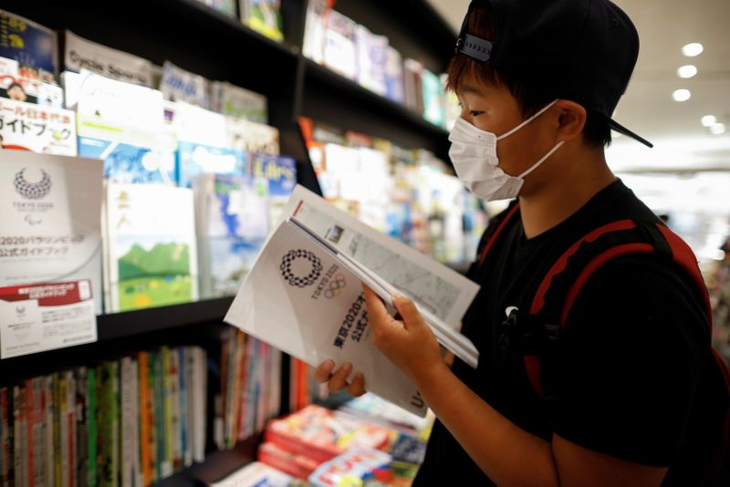 So Sato, a deaf and transgender pole vaulter, checks the official guide book for the Tokyo 2020 Olympic Games at a book store in Tokyo