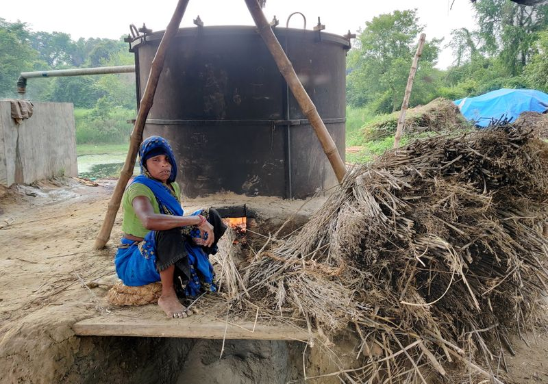 Manorami Rawat works at a furnace to extract peppermint oil in Dalipur
