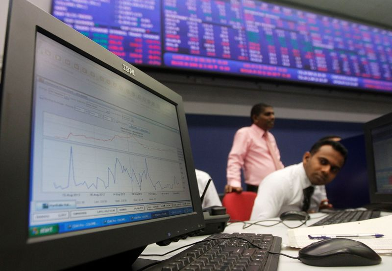 FILE PHOTO: A broker is pictured near a computer screen showing movements in the stock market since the morning opening at the Colombo Stock Exchange