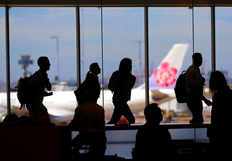 Passengers walk with their luggage towards departure gates at Sydney International Airport