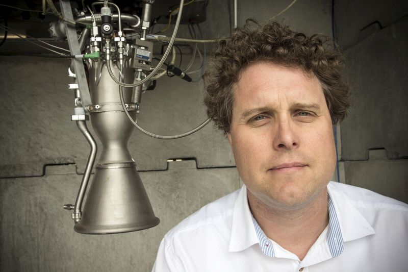 Rocket Lab CEO Peter Beck poses alongside a Rutherford rocket engine in Auckland