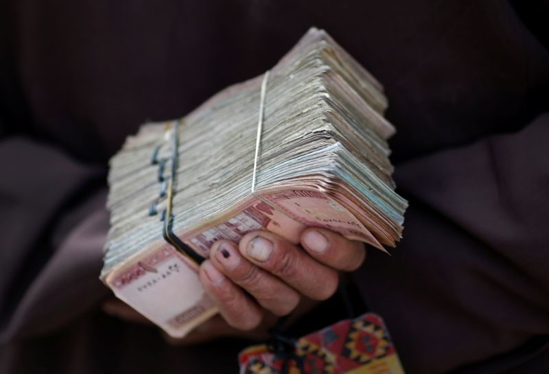 FILE PHOTO: Money changer holds a stack of Afghan currency on a street in central Kabul