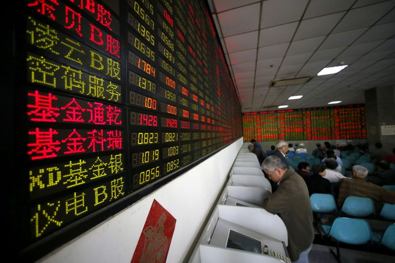 FILE PHOTO: Investors look at computer screens showing stock information at a brokerage house in Shanghai