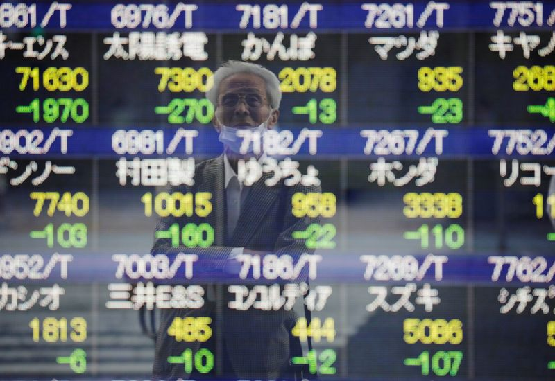 FILE PHOTO: A man wearing a protective mask, amid the COVID-19 outbreak, is reflected on an electronic board displaying stock prices outside a brokerage in Tokyo