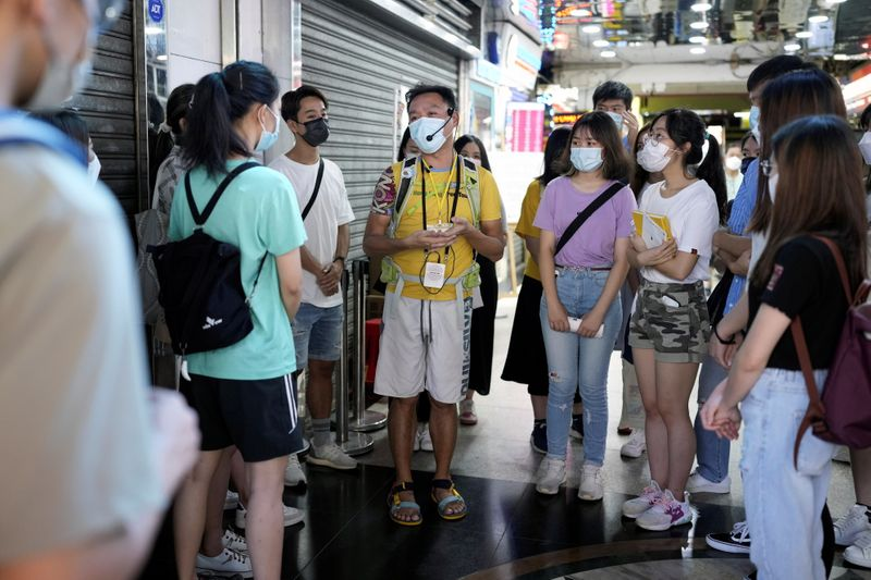 Tour guide Michael Tsang speaks to tourists during a tour visiting refugee communities in Hong Kong