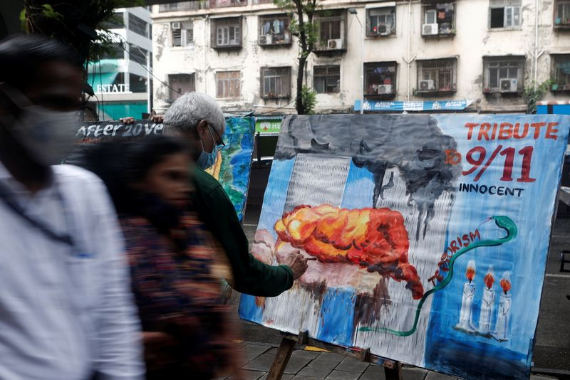 People walk past a 9/11 tribute on the 20th year anniversary outside an art school in Mumbai