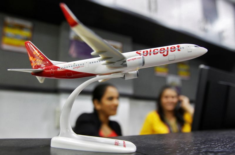 FILE PHOTO: Employees work inside a travel agency office beside a model of a SpiceJet aircraft in Ahmedabad