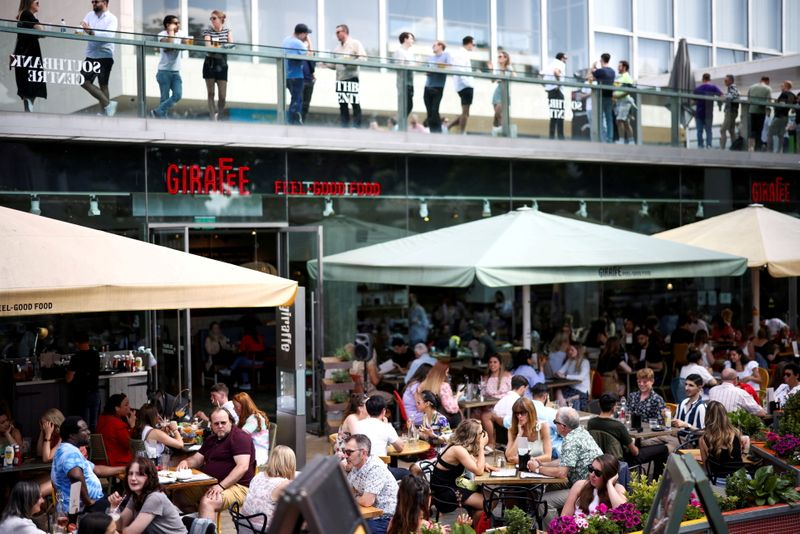 FILE PHOTO: People sit at an outdoor restaurant on the South Bank during sunny weather in London, Britain