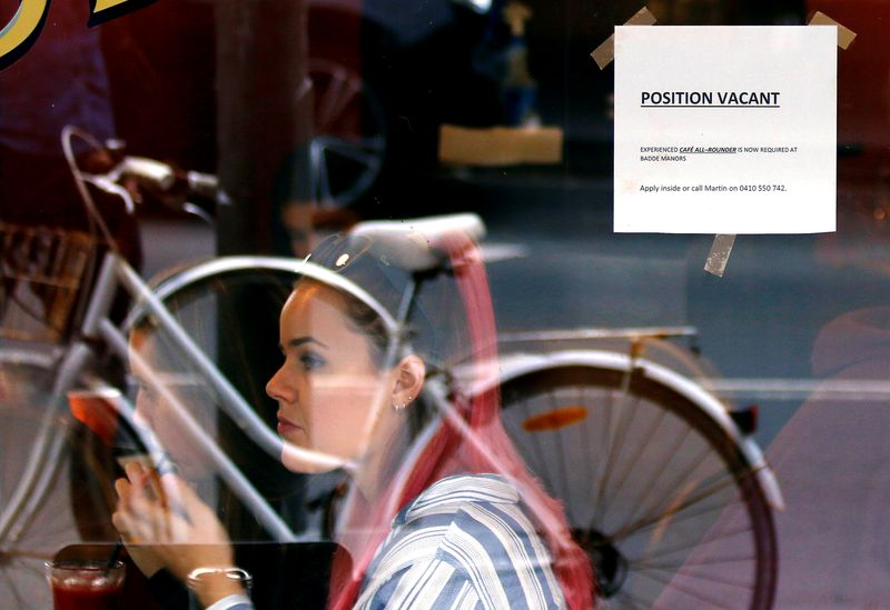 Customers at a local cafe are seen through a window displaying a job vacancy notice in central Sydney, Australia