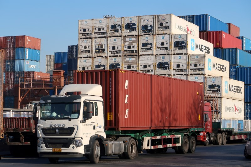 FILE PHOTO: Worker drives a truck carrying a container at a logistics center near Tianjin port