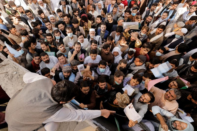 Afghans gather outside the passport office after Taliban officials announced they will start issuing passports to its citizens again