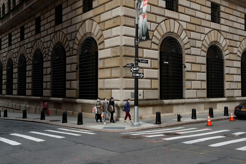 FILE PHOTO: People walk wearing masks outside The Federal Reserve Bank of New York in New York