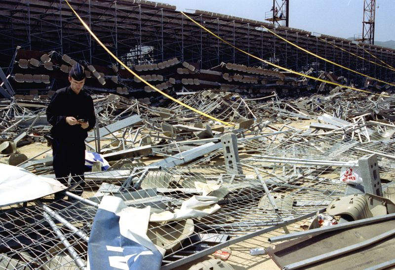 FILE PHOTO: MAY 94 - A policeman walks through the wreckage of the stand at Bastia's Furiani football..