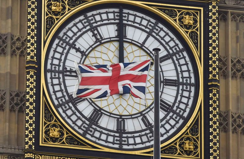 FILE PHOTO: A British Union flag flutters in front of one of the clock faces of the 'Big Ben' clocktower of The Houses of Parliament in central London