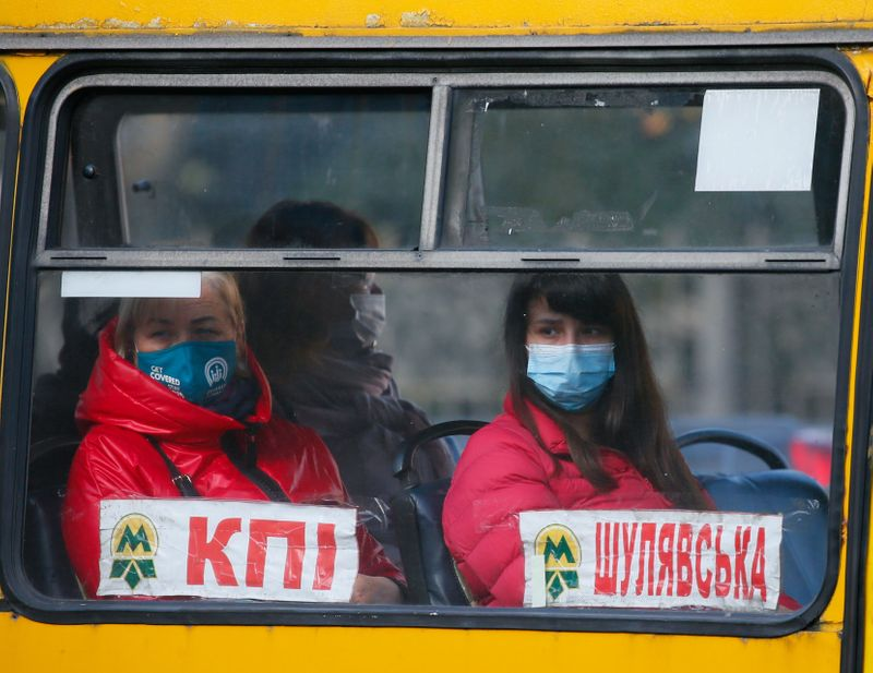 People wear protective face masks are seen in a bus in Kyiv